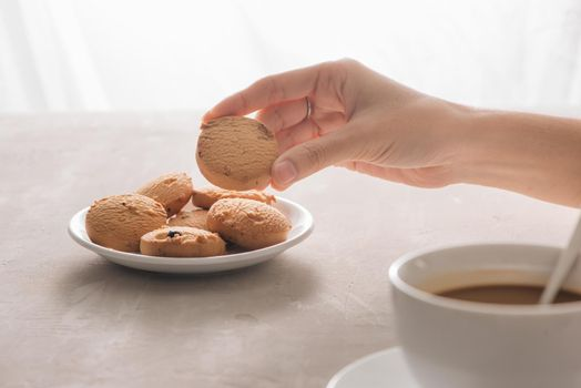 Hand picking cookie from plate. Drink with caffeine or cocoa with milk.