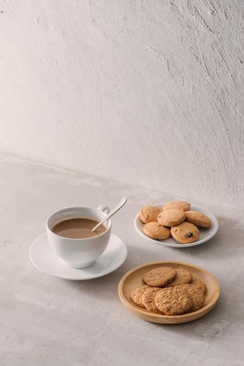 Cup of coffee with milk or cappuccino with cookies on light stone background. Drink with caffeine or cocoa with milk. Coffee break concept.