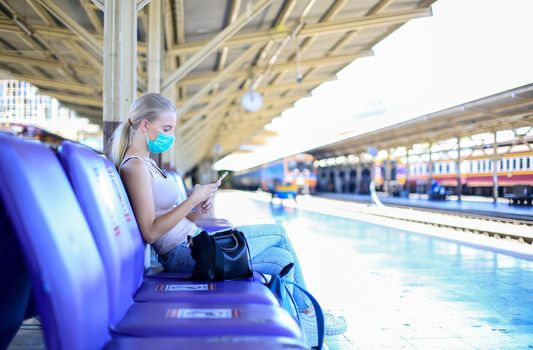 Portrait of confident young woman traveling by train, and wear protective face mask to prevent the spread of coronavirus, Covid-19
