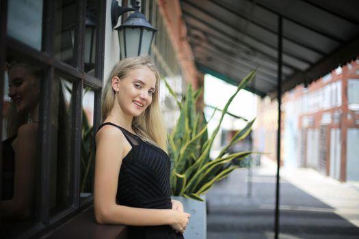 Portrait of Beautiful blonde hair girl on black dress as fashion portrait outdoor