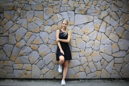 Portrait of Beautiful blonde hair girl on black dress against stone wall as fashion portrait outdoor.