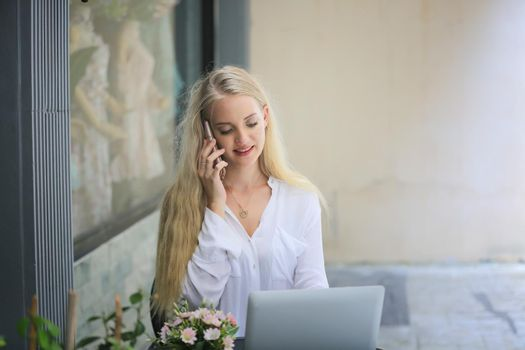 Beautiful blonde hair girl speaking on mobile phone with laptop on table outside coffee shop.