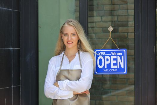 Portrait of confident young female shop, owner of small business coffee shop standing at shop front with open sign.