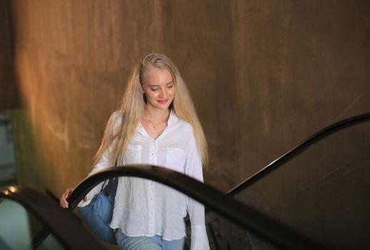 Beautiful blonde girl walking up the escalator.