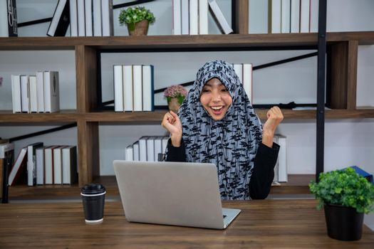 young Muslim woman using a laptop in a modern office