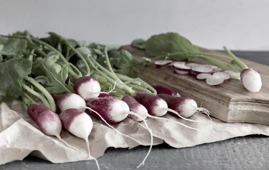 Young radish with green leaves on the table.