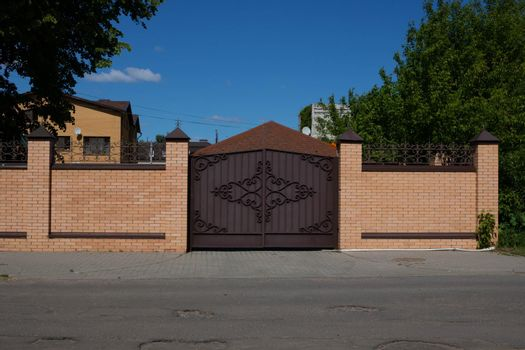 Light brick fence with iron wrought iron gates on the street against a background of wood and blue sky