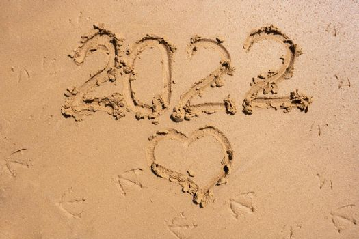 The numbers 2022 and the heart on the wet sand. The concept of the New Year 2022. Summer holidays and sea trips