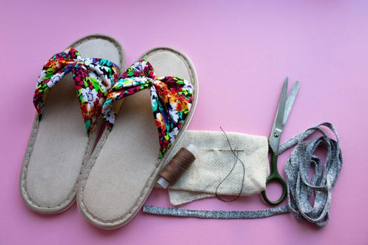 Thread needle scissors and colored home women's slippers on a pastel paper-pink background. Top view. Copy space