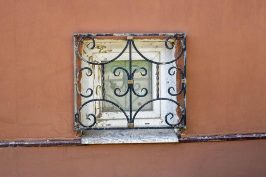 A window with antique bars on the plinth .Red facade with a small window