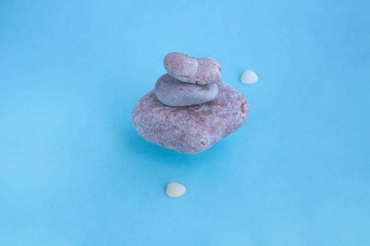 A stack of floating pink stones and small shells on a blue background. The concept of a relaxing massage for health