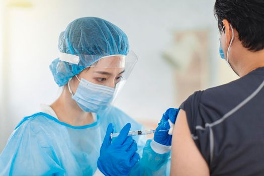 The doctor or nurse wears gowns, masks, and eye masks to help a patient in the injection