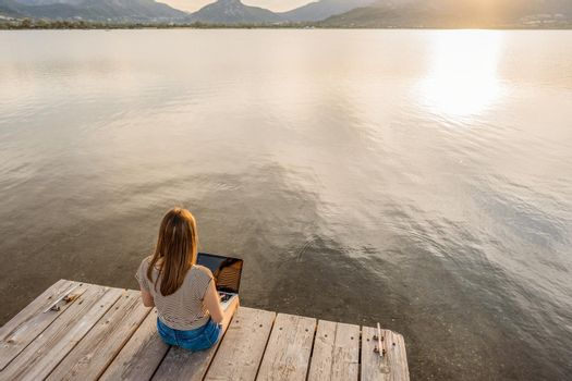 Lonely girl expressing her creativeness writing romance tales book on a wooden pier or jetty at sunset or dawn. New job opportunity at modern times using laptop and wifi internet connection technology