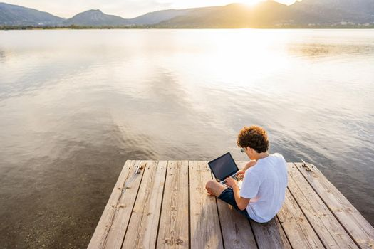 Nerd guy spending time outdoor programming at sunset writing code using laptop. New job opportunity at modern times to work everywhere using notebook and wifi 5g or 4g internet connection technology