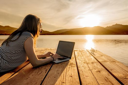 Young woman enjoying her creativeness writing book on a pier at sunset. New job opportunity at modern times to work everywhere using laptop and wifi internet connection technology. Girl studying