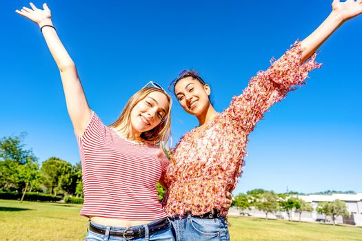 Two happy girls embracing each other with open up arms smiling looking at camera in a city park field in sunny day with blue sky. Mixed young women couple enjoying nature celebrating their diversity