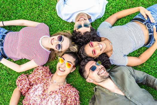 Group of friends lying on park meadow wearing colored trendy sunglasses looking at camera laughing. Happy diverse international people enjoying friendship in nature resting in circle. Mixed race union
