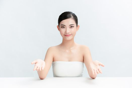 Best product. Young woman sitting at dressing table against white background and showing cosmetics product with smile