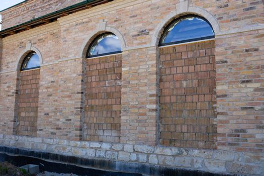 On the facade, arched windows are laid with brown brick