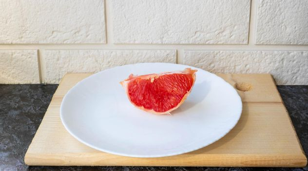 Healthy eating. Fresh healthy grapefruit on a white plate on the kitchen table. Creative concept of minimal food. Grapefruit Citrus Slices