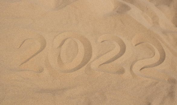 The numbers 2022 in the sand. The concept of the New Year 2022. Summer holidays and sea trips