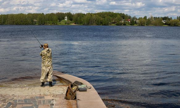 A fisherman in camouflage catches fish in the spring river