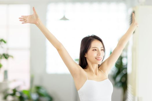 Young woman smiling and  taking a deep breath  in living room at morning