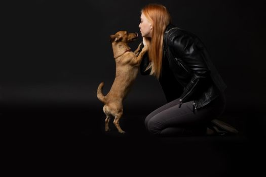Beautiful young woman is kissing her dog.