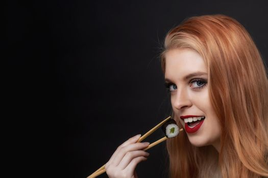 Side view portrait of young woman tasting sushi closeup.