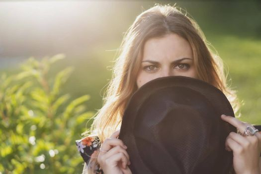 Portrait of beautiful girl hiding her face behind hat.