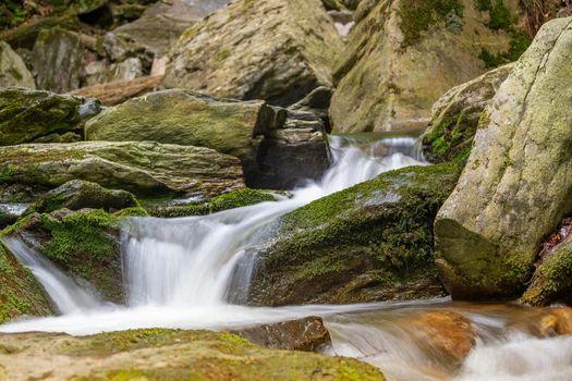 Silky effect of cascades of running water in a brook closeup.