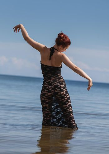 Nude woman in black lace dress against the sea