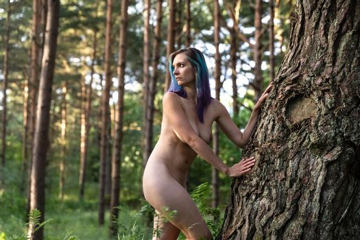 Naked woman in the forest near an old tree