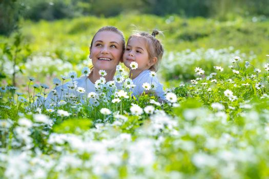 Nice Young Mother with Cute Little Son Having Fun in Fresh Daisy Flower Field. Spending Happy Active Summer Holidays in Countryside.