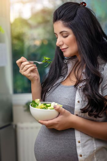 Happy Nice Pregnant Woman With Pleasure Eating Fresh Green Salad at Home. Diet For a Future Mother. Healthy Pregnancy Concept.