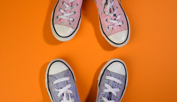 two pairs of textile sneakers on an orange background stand opposite each other. Dialogue and confrontation concept
