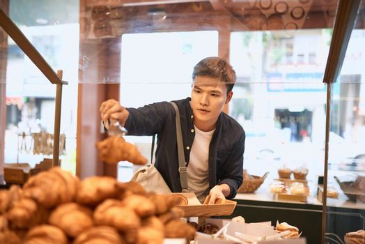 food, sale, consumerism and people concept -  handsome man with tray at bakery store buying buns or pies