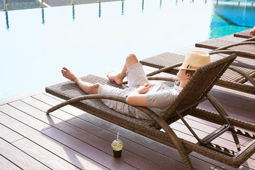 Lazy time. Asian guy sleeping on the couch swimming pool in summer