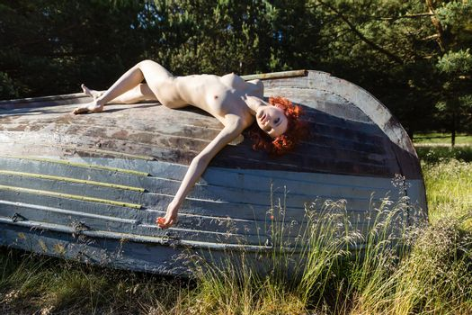 Naked woman posing outdoors in an old wooden boat