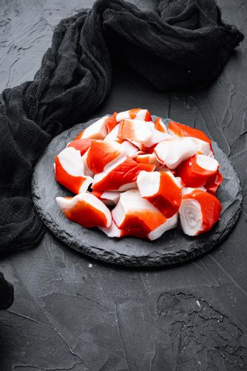 Fresh Crab meat surimi with blue swimming crab, on stone board, on black background