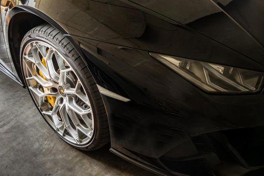 Bangkok, Thailand - 06 Jun 2021 : Close-up of Headlights, Wheel, and Rim of Black lamborghini sports car. Selective focus.