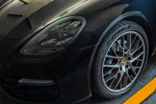 Bangkok, Thailand - 06 Jun 2021 : Close-up of Headlights, Wheel, and Rim of Black porsche sports car. Selective focus.