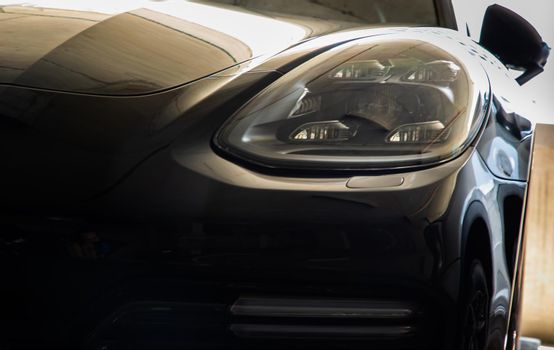 Bangkok, Thailand - 06 Jun 2021 : Close-up of Headlights of Black porsche car. Selective focus.