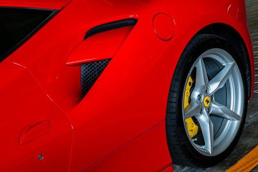Bangkok, Thailand - 06 Jun 2021 : Close-up of Rear wheel, and Rim of Red metallic Ferrari car. Selective focus.