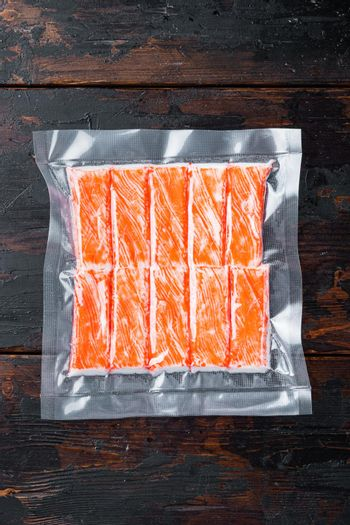 Crab sticks in vacuum pack, on dark wooden background, top view flat lay