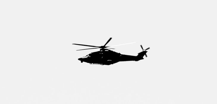 Military helicopter flying over the sky of the Spanish coast. Monochrome picture.