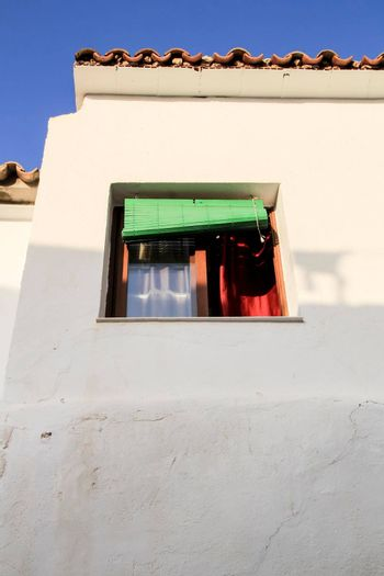 Whitewashed facade with window with green wooden blind in Altea village, Alicante, Spain