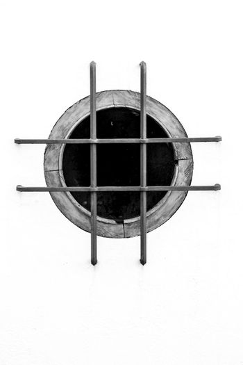 Whitewashed facade with circular window with forged metal grill in Altea village, Alicante, Spain. Monochrome picture