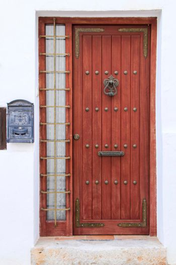 Beautiful whitewashed facade with old wooden door with iron details in Altea village, Alicante, Spain