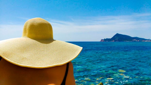 Woman in big white on Cap Negret beach on a sunny day of Spring in Altea, Alicante, Spain